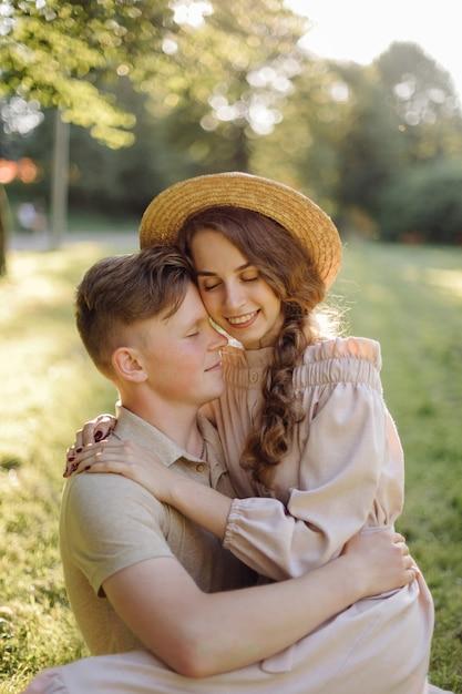 屋外の愛の若いカップル。フィールドでポーズをとって夏にスタイリッシュなファッションの若いカップルの見事な官能的な屋外のポートレート 無料写真