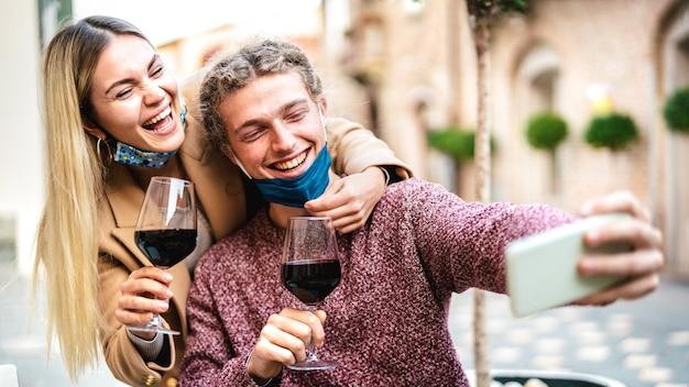 Молодая влюбленная пара с открытой маской для лица, делающая селфи в винном баре Premium Фотографии