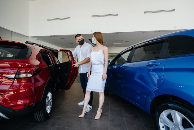 仮面をかぶった若いカップルが新しい車を選び、パンデミックの時期に販売店の担当者に相談します。 Premium写真