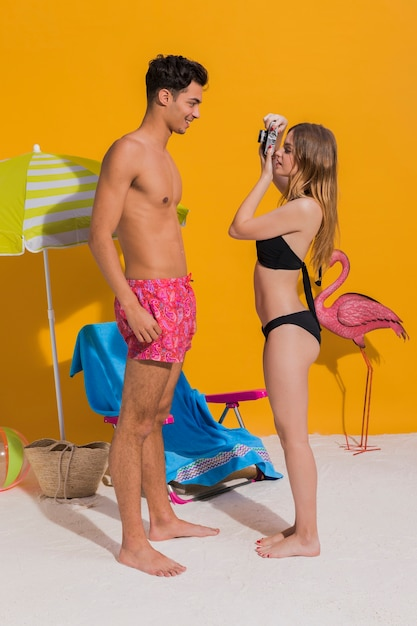 Молодая пара в купальных костюмах фотографирует Бесплатные Фотографии