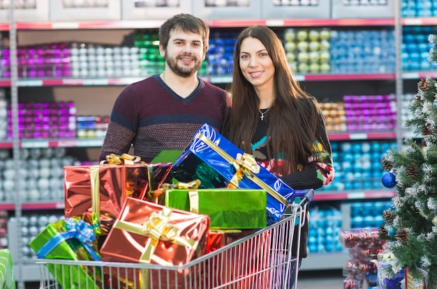 A young couple is shopping at the supermarket for the new year. Premium Photo