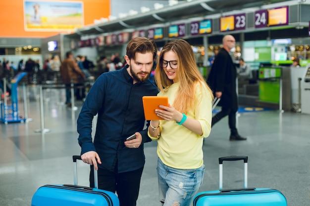 젊은 부부는 공항에서 두 가방 사이에 서 있습니다. 그녀는 긴 머리, 안경, 스웨터, 청바지를 가지고 있습니다. 그는 턱수염에 검은 색 셔츠와 바지를 입는다. 그들은 태블릿에서 읽고 있습니다. 무료 사진