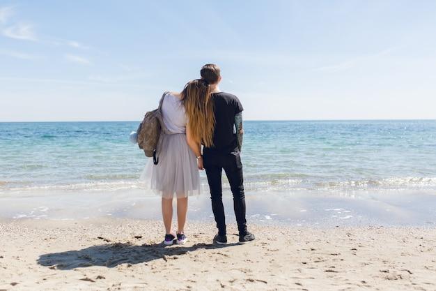 若いカップルは海のそばに立っています。 無料写真