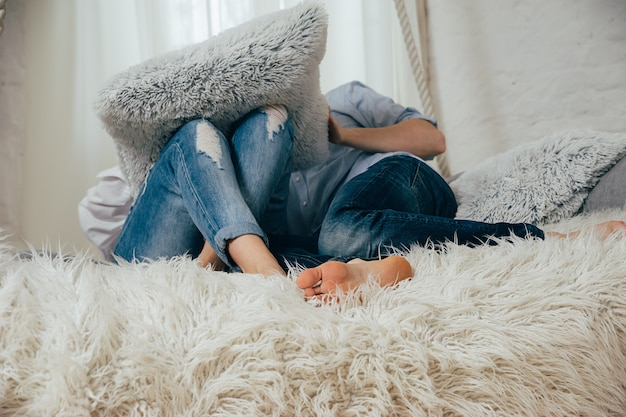 A young couple in jeans on a white bed Premium Photo