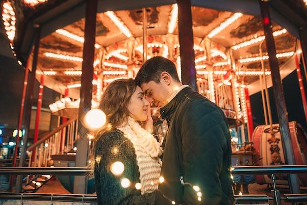 크리스마스 시간에 밤 거리에서 젊은 부부 키스와 포옹 야외 무료 사진