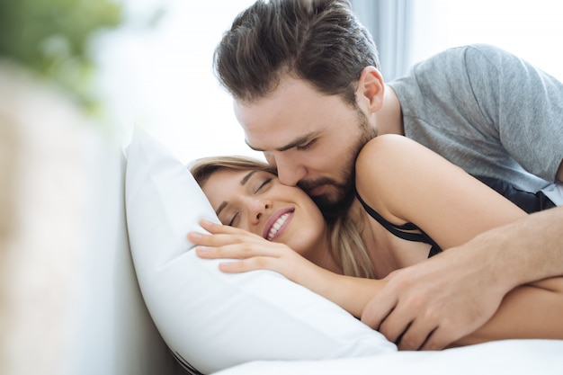 Young couple kissing cheek in the bed wake up in the morning. Premium Photo