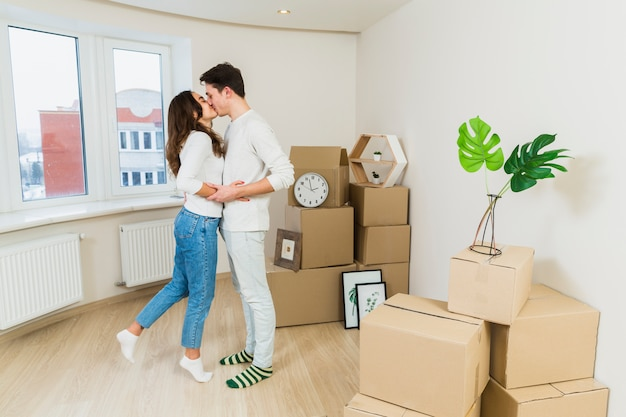 Young couple kissing each other with cardboard boxes in their new home Free Photo