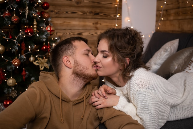 Young couple kissing at home at christmas time near beautifully decorated christmas tree Premium Photo