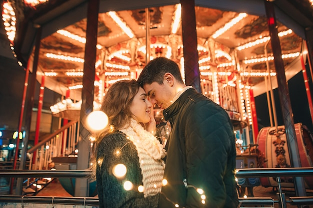 Young couple kissing and hugging outdoor in night street at christmas time Free Photo