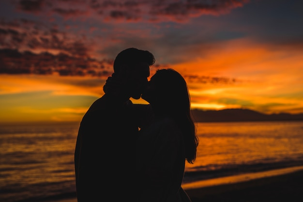 Young couple kissing on sea shore in evening Free Photo