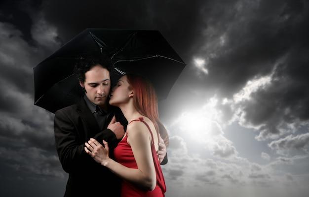 Young couple kissing under umbrella Premium Photo