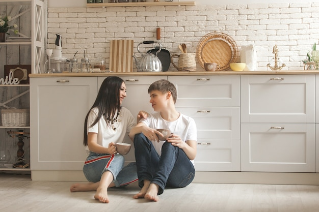 Young couple on the kitchen. man and woman cooking. boyfriend and girlfriend indoors on the kitchen. Premium Photo