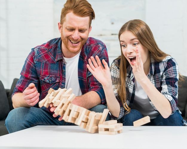Young couple looking at jenga tower collapses on white table surface Free Photo