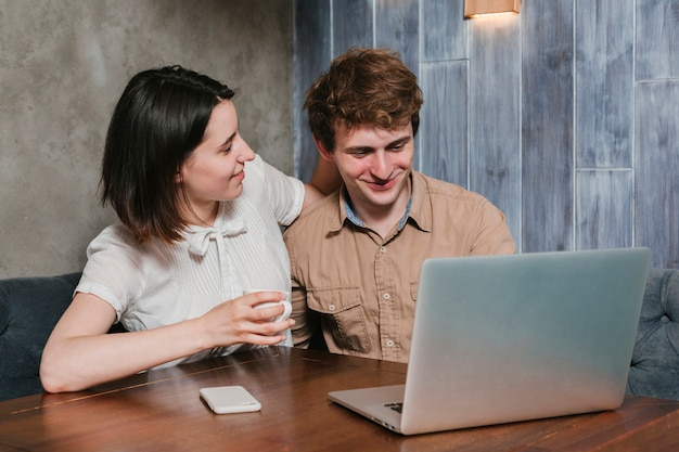 Young couple looking at the laptop smiling Free Photo