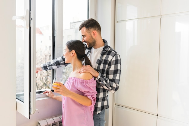 Young couple looking out of window at home Free Photo
