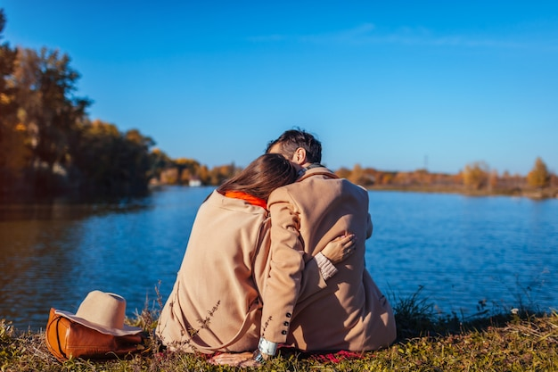 Young couple in love chilling by autumn lake and hugging Premium Photo