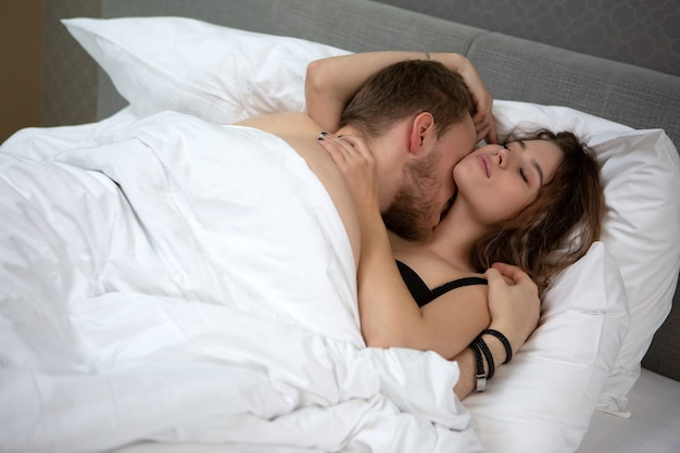 Premium Photo | Young couple in love passionately kissing in bed