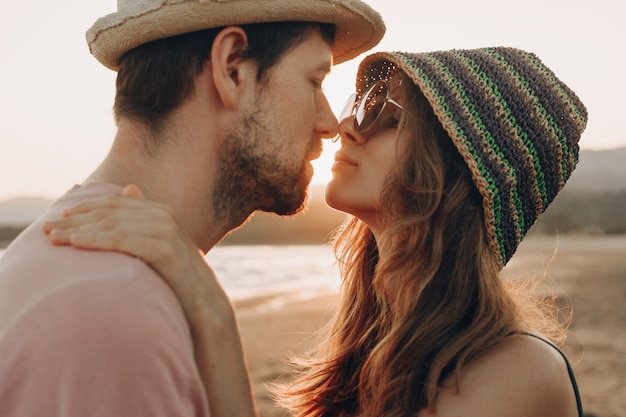 Young couple in love standing on the beach, enjoying sunset ocean. Free Photo