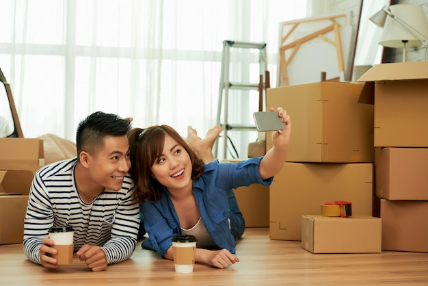 A young couple lying carefree on the floor taking selfie in front of packing boxes Free Photo