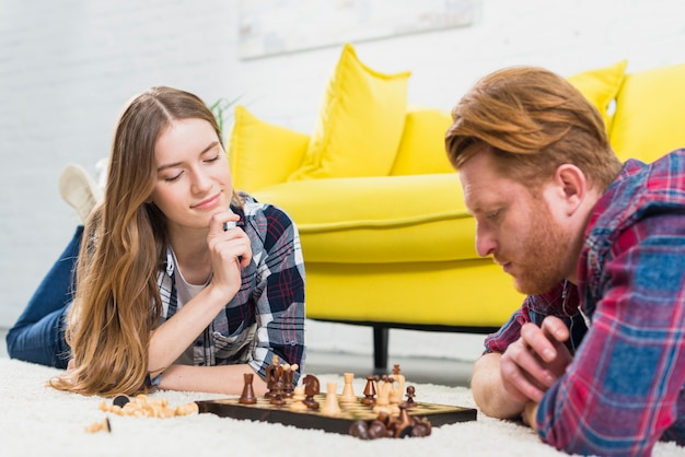 Young couple lying on carpet looking at chess board on the white carpet at home Free Photo