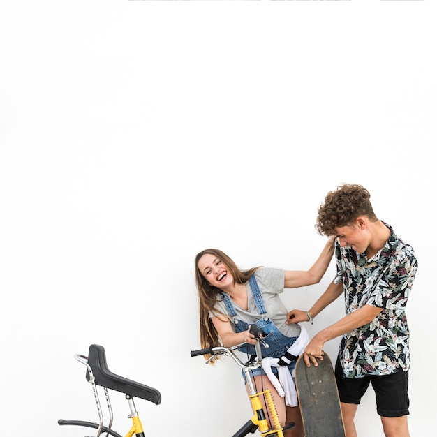 Young couple making fun with her girlfriend holding skateboard and bicycle Free Photo