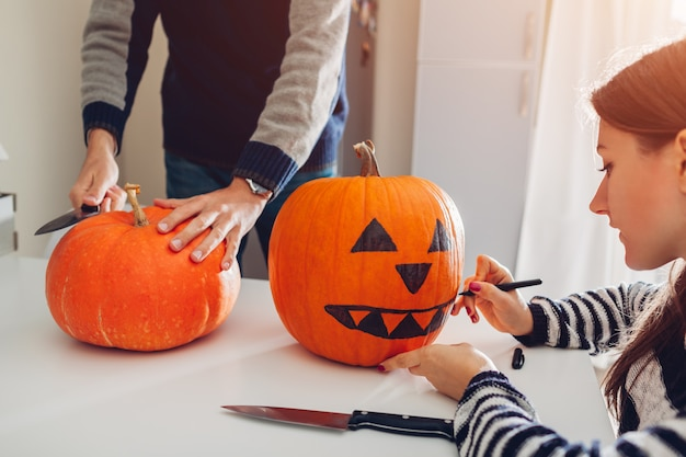 Young couple making jack-o-lantern for halloween on kitchen. drawing and cutting pumpkin Premium Photo