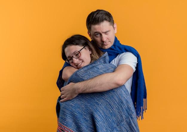 오렌지 벽 위에 서 심각한 얼굴로 따뜻한 담요와 그의 여자 친구를 덮고 사랑 남자에 행복 젊은 부부 남자와 여자 무료 사진