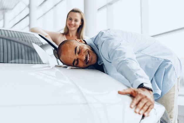 カーショップで新しい車を抱き締める若いカップルの男性と女性がクローズアップ Premium写真