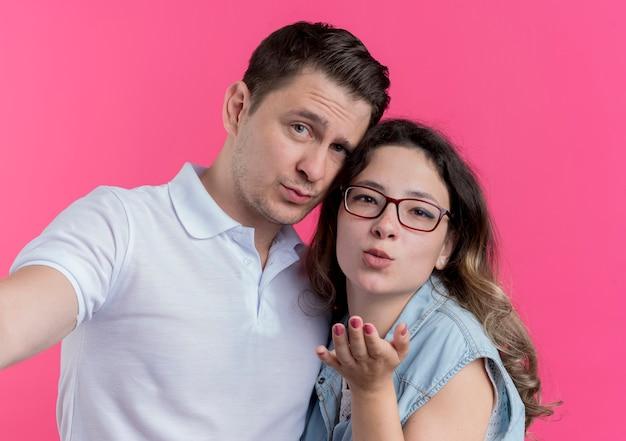 ピンクの壁を越えて彼女の前で手でキスを吹く愛の女性で幸せに一緒に立っているカジュアルな服を着た若いカップルの男性と女性 無料写真