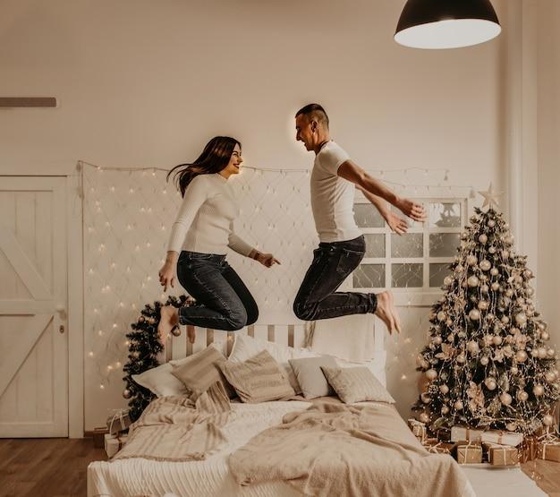 Молодая пара мужчина и женщина прыгают на кровати в спальне, украшенной деревом дом на новый год Premium Фотографии