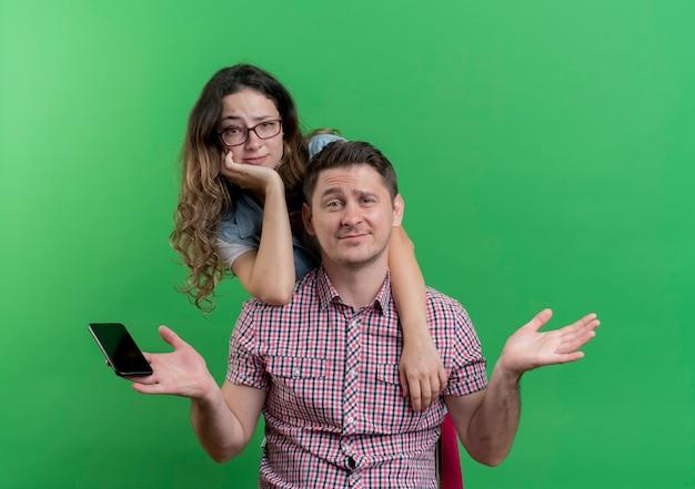 Giovane coppia uomo e donna in abiti casual uomo confuso tenendo lo smartphone e la sua ragazza in piedi dietro di lui che dà una occhiata fuori con espressione scettica sopra la parete verde Foto Gratuite