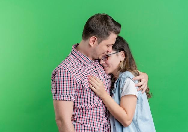 Giovane coppia uomo e donna in abiti casual felici nell'amore che abbraccia in piedi sopra la parete verde Foto Gratuite