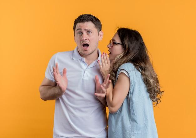 Giovane coppia uomo e donna in abiti casual donna che bisbiglia un segreto al suo ragazzo sorpreso in piedi sopra la parete arancione Foto Gratuite