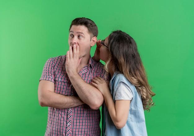 Giovane coppia uomo e donna in abiti casual donna che bisbiglia un segreto al suo ragazzo sorpreso in piedi sopra la parete verde Foto Gratuite