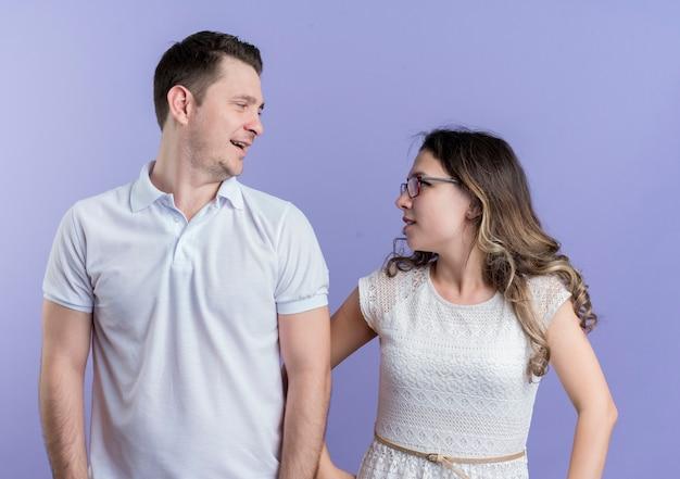 Coppia giovane uomo e donna guardando l'altro sorridente in piedi sopra la parete blu Foto Gratuite