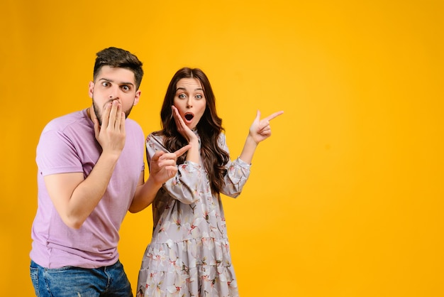 Young couple man and woman surprised pointing at copyspace Premium Photo