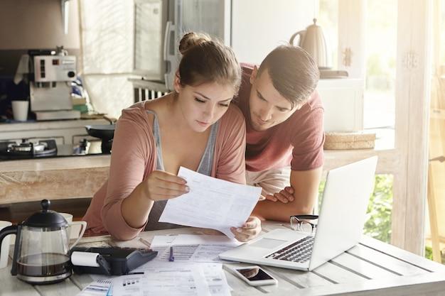 Молодая пара, управляющая финансами, просматривая свои банковские счета с помощью портативного компьютера и калькулятора на современной кухне. женщина и мужчина вместе делают документы Бесплатные Фотографии