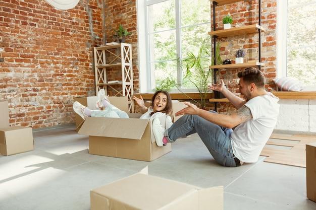 La giovane coppia si è trasferita in una nuova casa o appartamento. divertirsi con le scatole di cartone, rilassarsi dopo la pulizia e il disimballaggio nel giorno del trasloco. sembri felice. famiglia, trasloco, relazioni, concetto di prima casa. Foto Gratuite