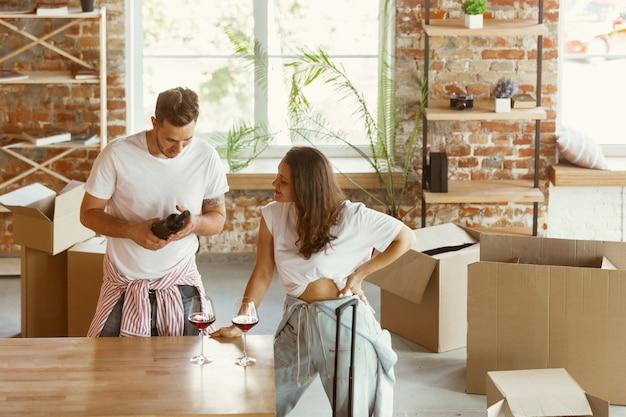 Молодая пара переехала в новый дом или квартиру. пить красное вино, улыбаться и расслабляться после уборки и распаковки. выглядите счастливым и уверенным. семья, переезд, отношения, концепция первого дома. Бесплатные Фотографии