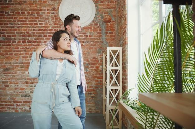 Молодая пара переехала в новый дом или квартиру. выглядите счастливым и уверенным. семья, переезд, отношения, концепция первого дома. думаю о будущем ремонте и отдыхе после чистки и распаковки. Бесплатные Фотографии