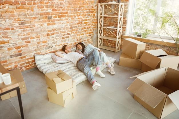 Молодая пара переехала в новый дом или квартиру. лежат вместе, отдыхают после уборки и распаковывают вещи в перенесенный день. выглядите счастливым, мечтательным и уверенным в себе. семья, переезд, отношения, концепция первого дома. Бесплатные Фотографии