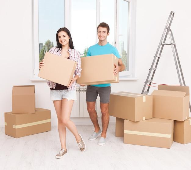 Молодая пара, перемещая коробки в новом доме Premium Фотографии
