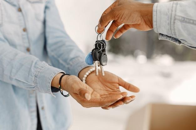 若いカップルが一緒に新しい家に移動します。段ボール箱とアフリカ系アメリカ人のカップル。女性はキーを押したままにします。 無料写真