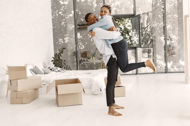 Молодая пара вместе переезжает в новый дом. афро-американская пара с картонными коробками. Бесплатные Фотографии