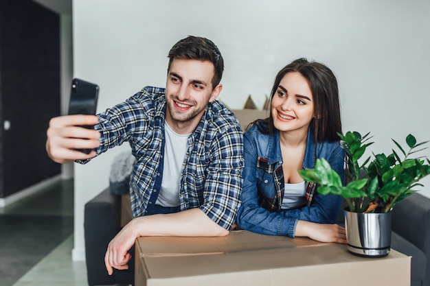 Young couple moving in new home and taking selfie. making selfie with smart phone in new apartment Premium Photo