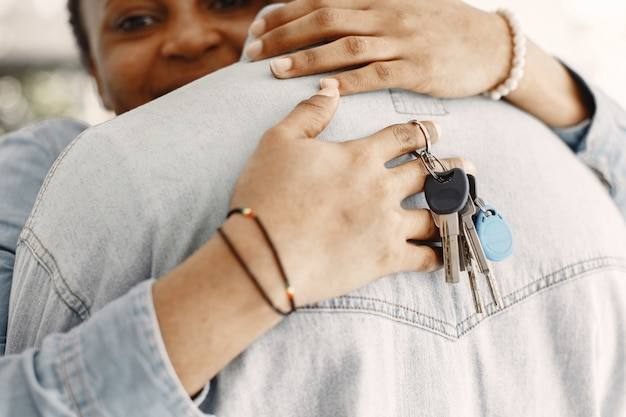 Young couple moving in to new home together. african american couple with cardboard boxes. woman hold keys. Free Photo