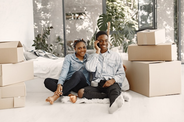 Young couple moving in to new home together. african american couple with cardboard boxes. Free Photo