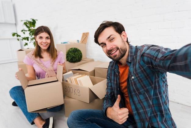 Young couple moving together in new house; unpacking cardboard boxes; taking sulfide Free Photo
