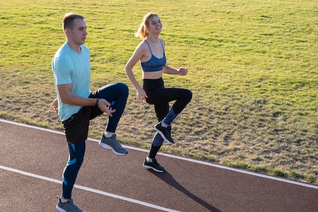 Молодая пара подходящих спортсменов, мальчик и девочка, бегающие во время упражнений на красных дорожках общественного стадиона на открытом воздухе. Premium Фотографии