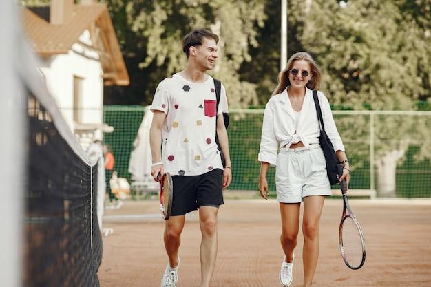 Молодая пара на теннисном корте. два теннисиста в спортивной одежде. Бесплатные Фотографии